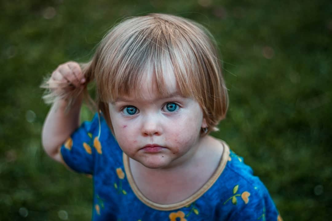 A close up of a small child in a blue shirt