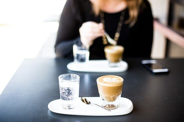 A person sitting at a table with a cup of coffee