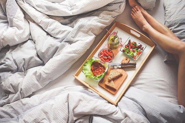A person sitting on a bed with breakfast food
