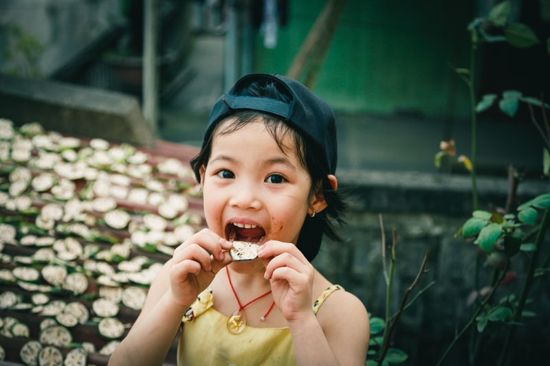 A little girl that is eating some food